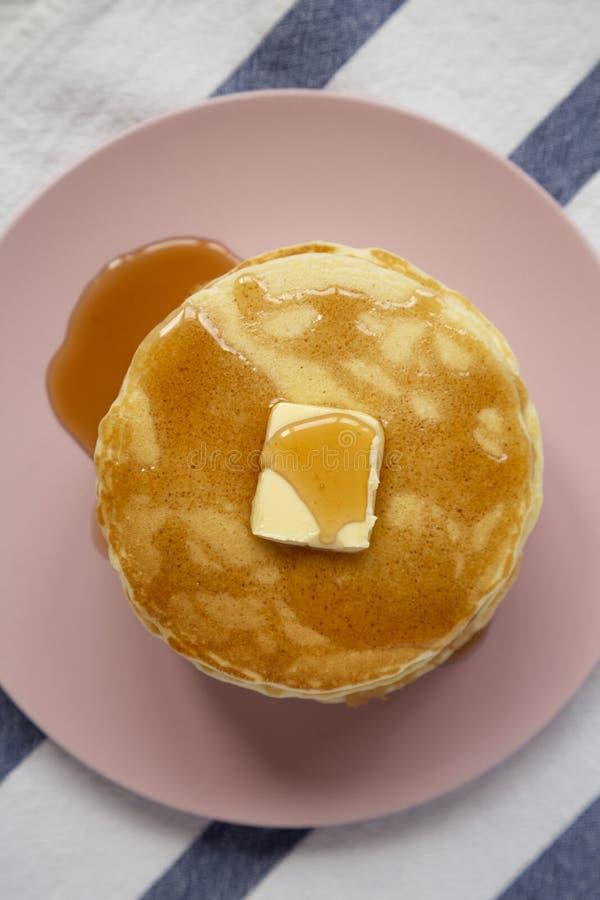 Över huvudet sikt, bunt av hemlagade pannkakor med smör och lönnsirap på en rosa platta ?ver huvudet b?sta sikt, lekmanna- l?genh royaltyfri bild