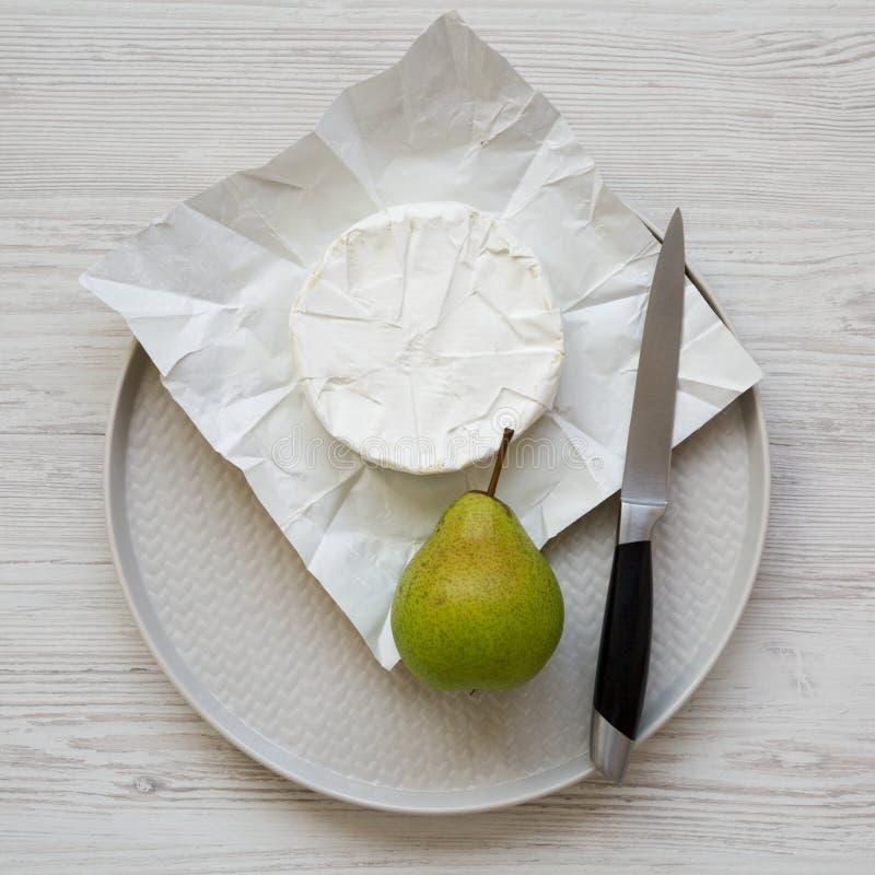 Över huvudet sikt, camembertost och nytt päron på en platta på en vit träyttersida Mat f?r vin Lekmanna- l?genhet, b?sta sikt, fr royaltyfri foto