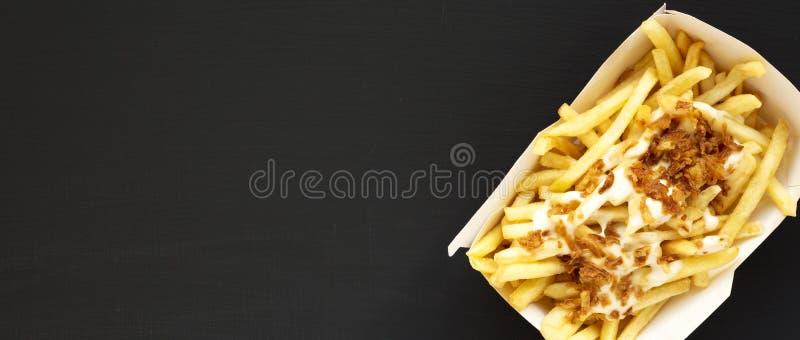 Över huvudet sikt, franska småfiskar med ostsås och lök i en pappers- ask på en svart bakgrund Lekmanna- l?genhet, ?ver huvudet b arkivfoto