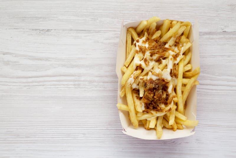 Över huvudet sikt, franska småfiskar med ostsås och stekt lök i en pappers- ask på en vit träyttersida L?genheten l?gger, fr?n ov fotografering för bildbyråer