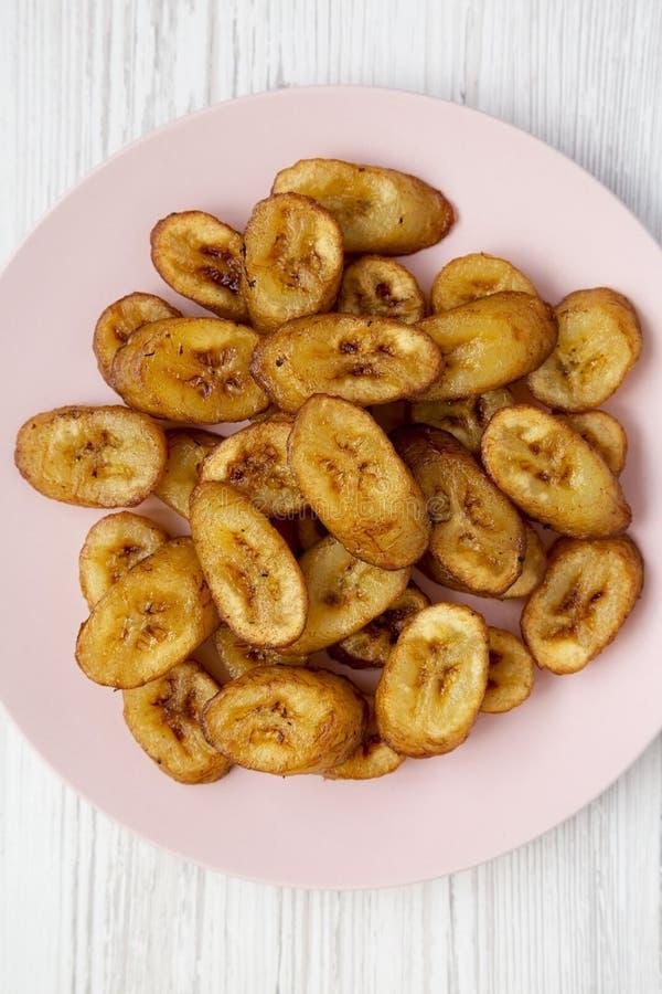 Över huvudet sikt, hemlagade stekte pisang på en rosa platta över vit träbakgrund Lekmanna- l?genhet, ?ver huvudet, fr?n ?ver N?r royaltyfri bild