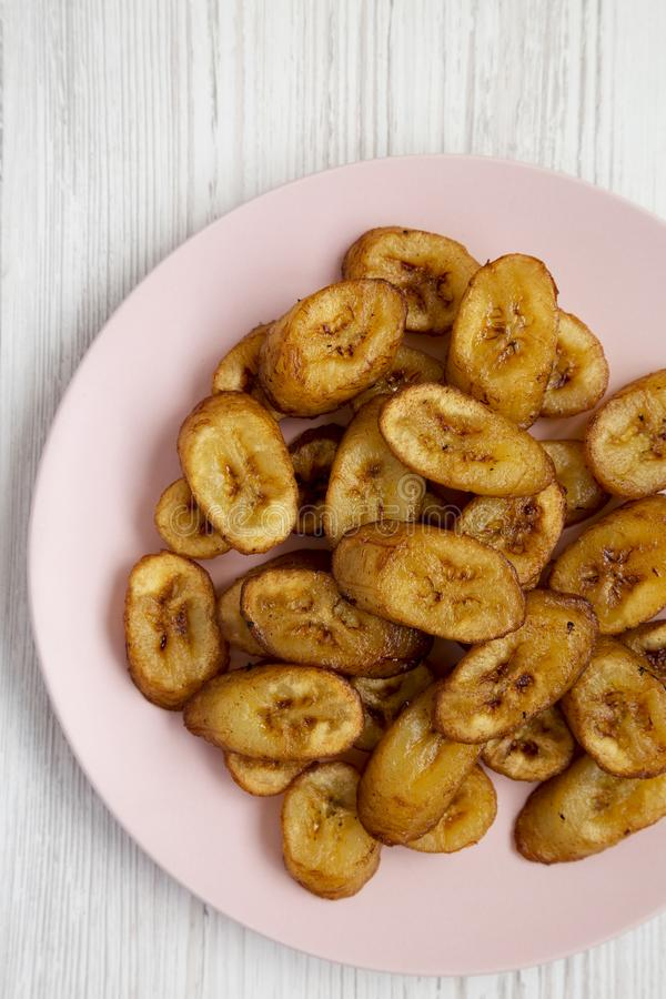 Över huvudet sikt, hemlagade stekte pisang på en rosa platta på en vit träyttersida Lekmanna- l?genhet, ?ver huvudet, fr?n ?ver N royaltyfri fotografi