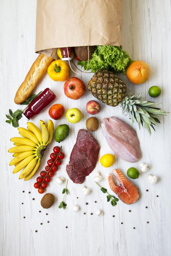 Över huvudet sikt, pappers- påse av olika frukter och grönsaker på en vit träyttersida Sund matbakgrund, b?sta sikt Sunt royaltyfri bild
