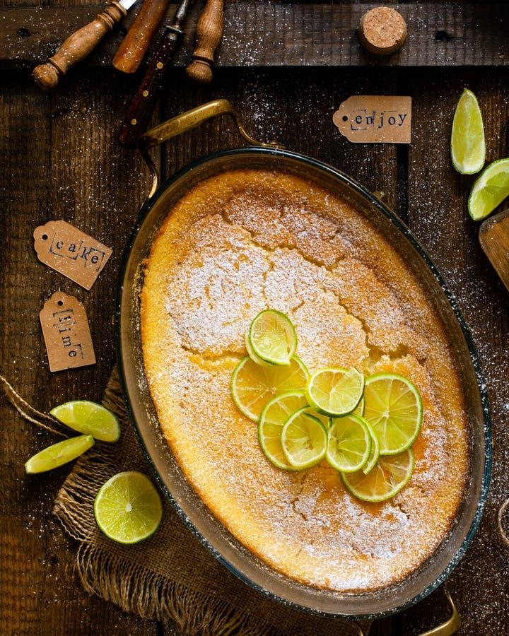 Över huvudet skott av den hemlagade eldfasta formen, pudding, ostkaka, syrligt, paj eller mousse med skivor av limefrukt överst i royaltyfri foto