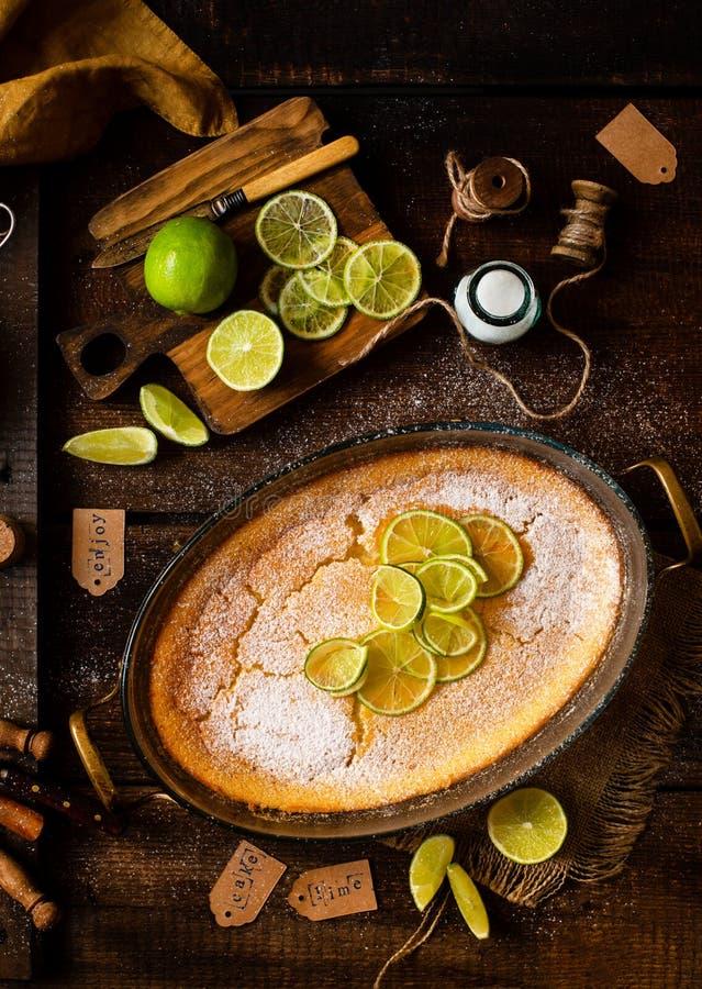 Över huvudet skott av den hemlagade eldfasta formen, pudding, ostkaka, syrligt, paj eller mousse med skivor av limefrukt överst i arkivfoto
