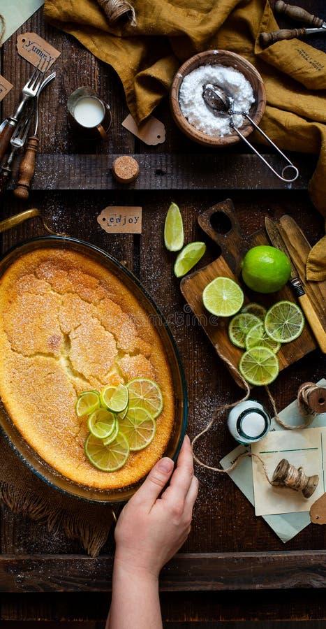Över huvudet skott av den hemlagade eldfasta formen, pudding, ostkaka, syrligt, paj eller mousse med skivor av limefrukt överst royaltyfri bild