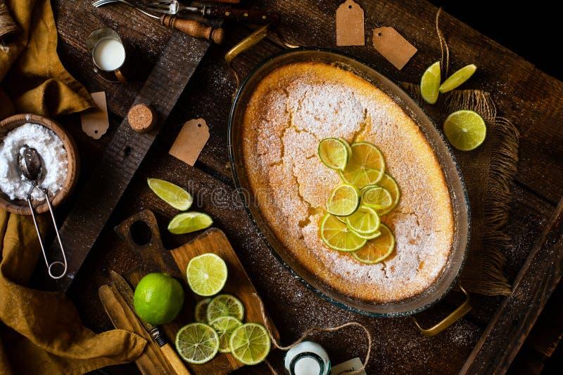 Över huvudet skott av den hemlagade eldfasta formen, pudding, ostkaka, syrligt, paj eller mousse med skivor av limefrukt i oval e arkivfoto