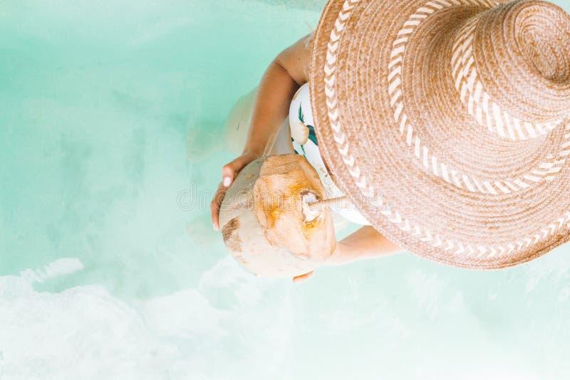 Över huvudet skott av en kvinnlig i en stor hatt som dricker en exotisk smaklig drink, medan stå i vatten fotografering för bildbyråer