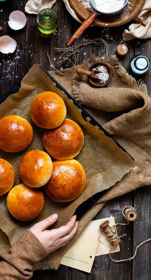 Över huvudet skott av hemlagade bakade smakliga bullar för hamburgare eller frukost på bakplåten med pergament arkivfoton