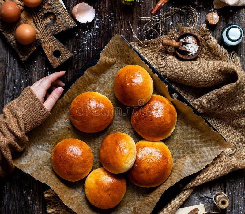 Över huvudet skott av hemlagade bakade smakliga bullar för hamburgare eller frukost på bakplåten med pergament royaltyfria foton