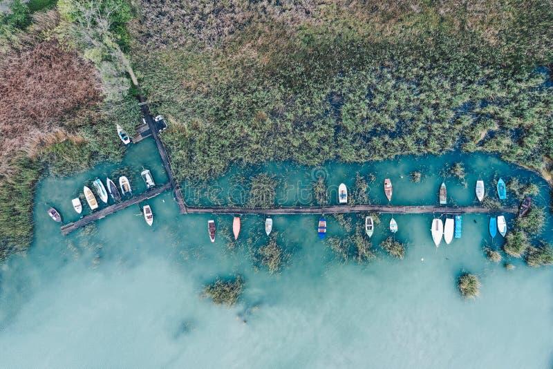 Över huvudet skott av lite skeppsdockan på kusten med parkerade fiskebåtar royaltyfri foto