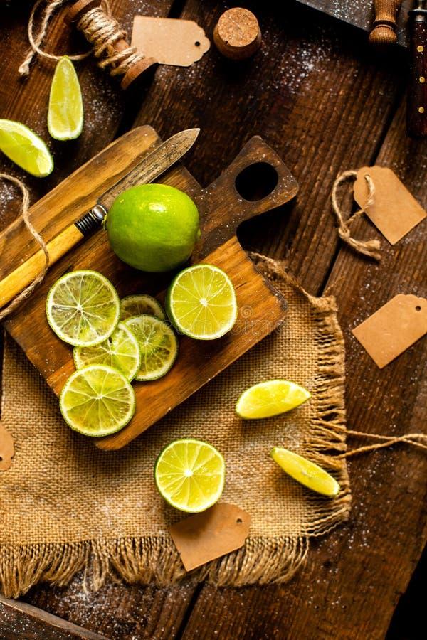 Över huvudet skott av saftiga skivade och hela limefrukter på träbrädeställningar på den lantliga bruna tabellen royaltyfri foto