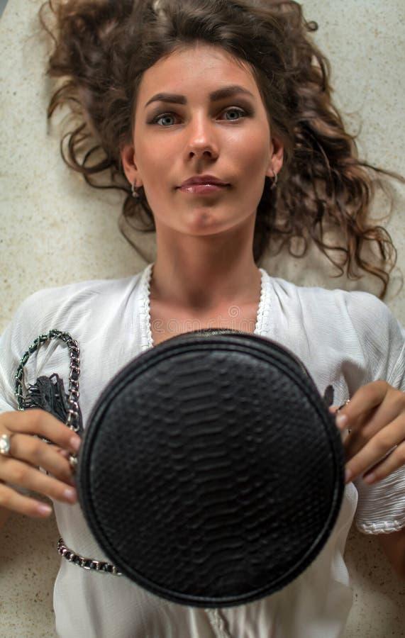 Över huvudet ståendesikt av en härlig ung kvinna som lägger ner i hennes dyra villa med den luxuty pytonormpåsen Ha lockigt hår, arkivfoto