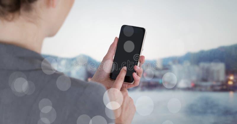 Över skuldraaffärskvinnan med telefonen mot oskarp horisont med bokeh fotografering för bildbyråer