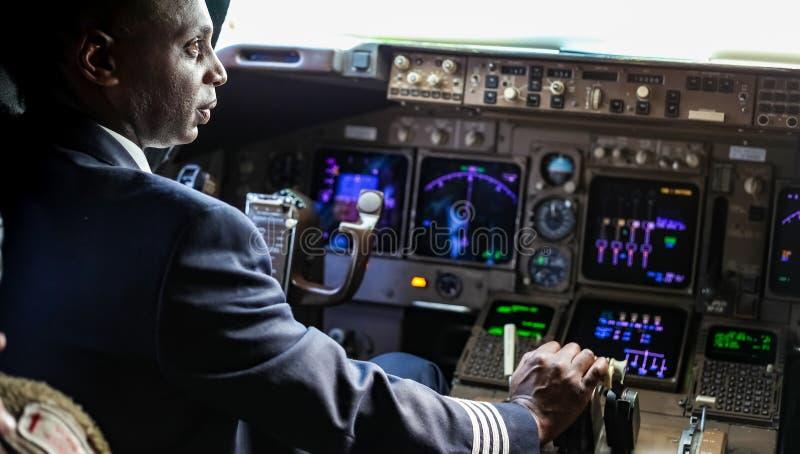 Över skuldran av en afrikansk pilot i en jumbocockpit arkivbild