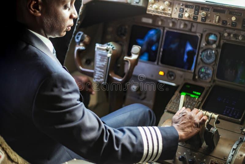 Över skuldran av en afrikansk pilot i en jumbocockpit royaltyfri bild