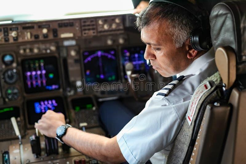 Över skuldran av en indisk pilot i en jumbocockpit fotografering för bildbyråer