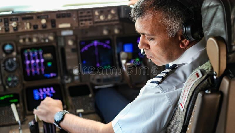 Över skuldran av en indisk pilot i en jumbocockpit royaltyfri foto