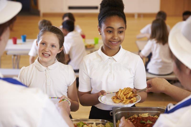 Över skuldrasikt av flickor som tjänas som i skolakafeteria royaltyfri foto
