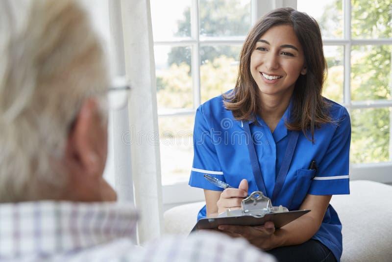 Över skuldrasikt av sjuksköterskan på hem- besök med den höga mannen royaltyfri foto