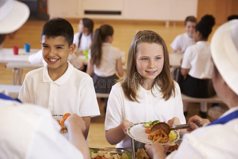 Över skuldrasikt av ungar som tjänas som i skolakafeteria royaltyfri fotografi