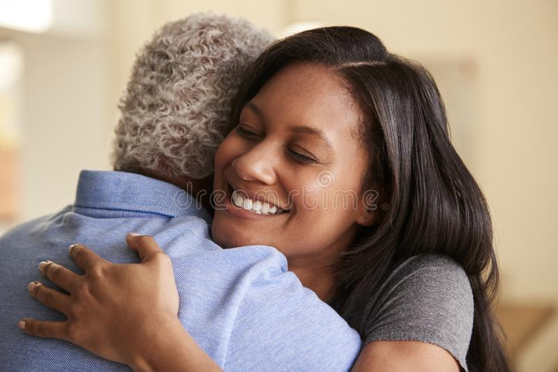 Över skuldrasikten av Being Hugged By för hög fader den vuxna dottern hemma royaltyfri foto
