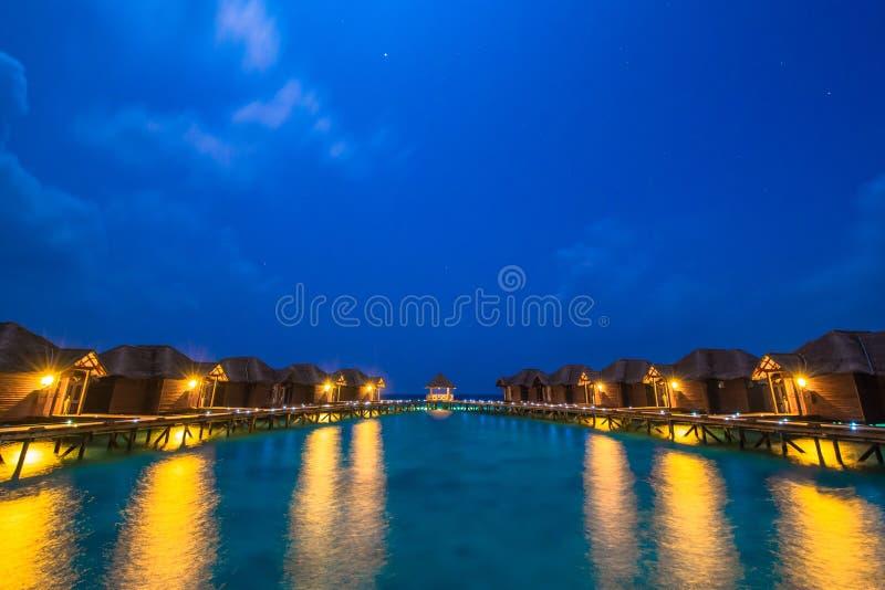 Över vattenbungalower med moment in i den fantastiska gröna lagun royaltyfri foto