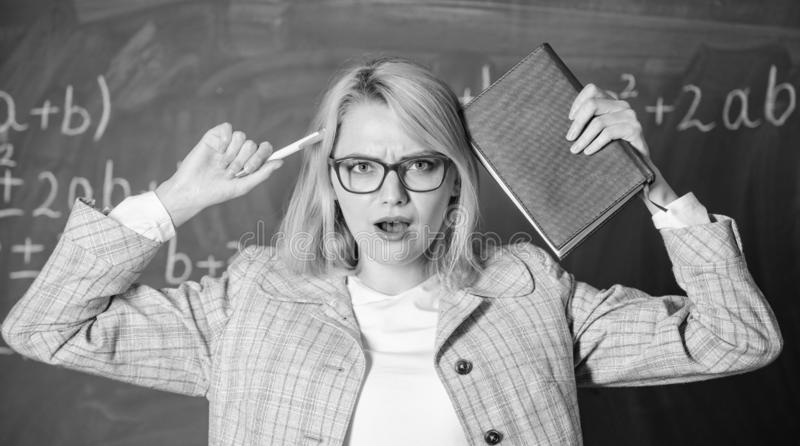 Överanstränga och brist av service som kör läraren ut ur yrke Lärarekvinna med svart tavlabakgrund för bok varför royaltyfria foton