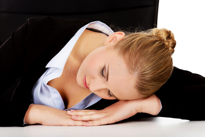 Överansträngd affärskvinna som i regeringsställning sover på skrivbordet royaltyfri bild