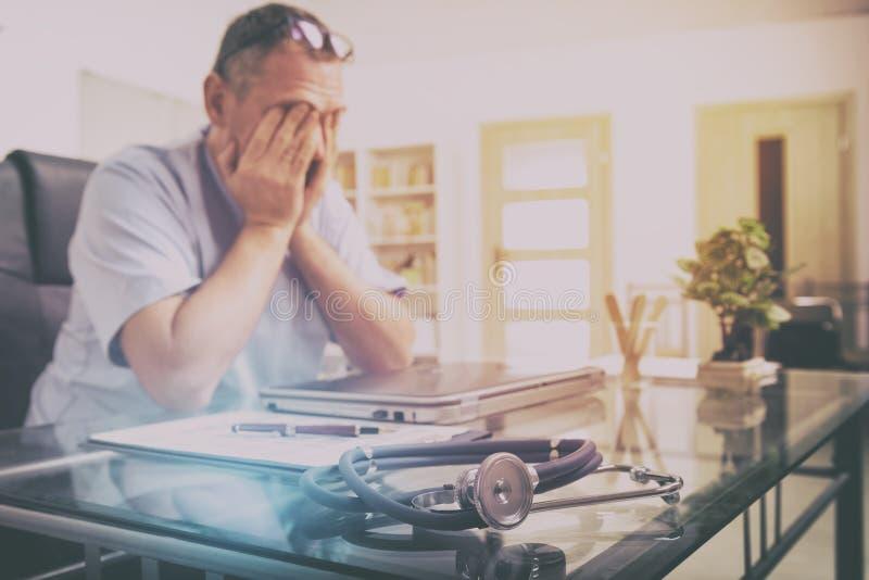 Överansträngd doktor i hans kontor arkivfoton