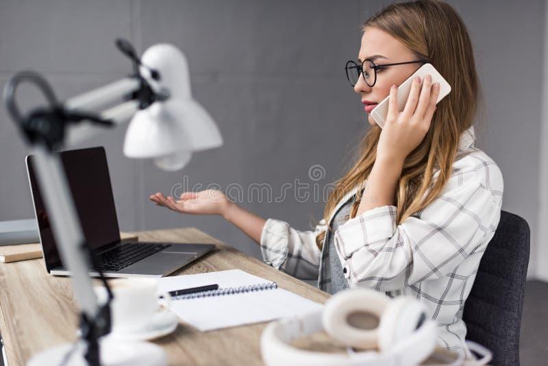 överansträngd ung affärskvinna som talar vid telefonen på arbetsplatsen och att se arkivfoto