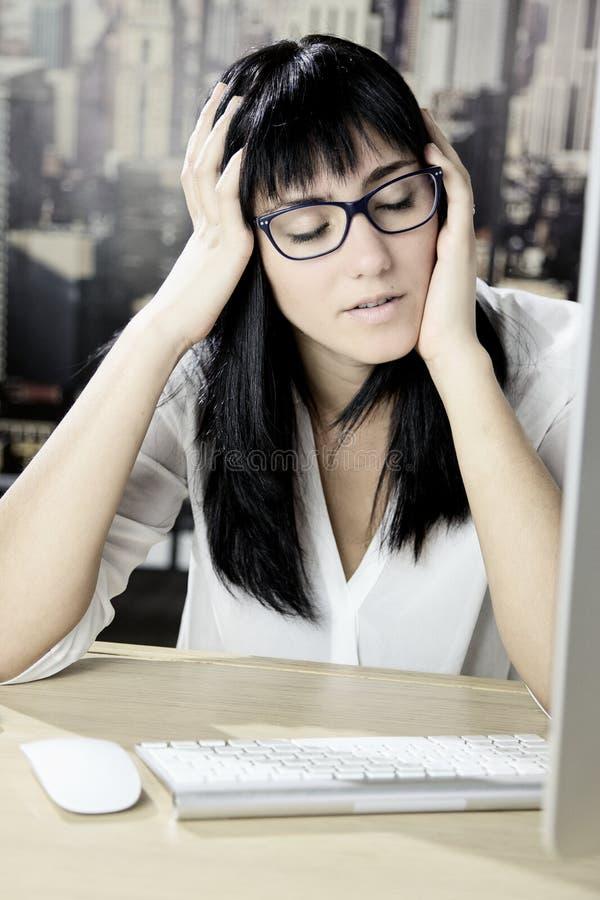 Överansträngd ung kvinna framme av datoren med huvudvärk royaltyfria foton