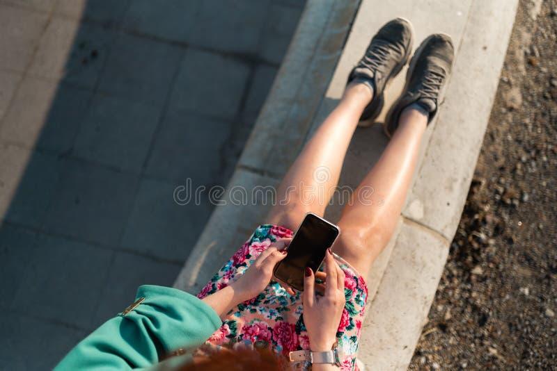 Överblicken av en ung kvinna använder telefonen i en slott parkerar att sitta på en springbrunn - sikt från över fotografering för bildbyråer