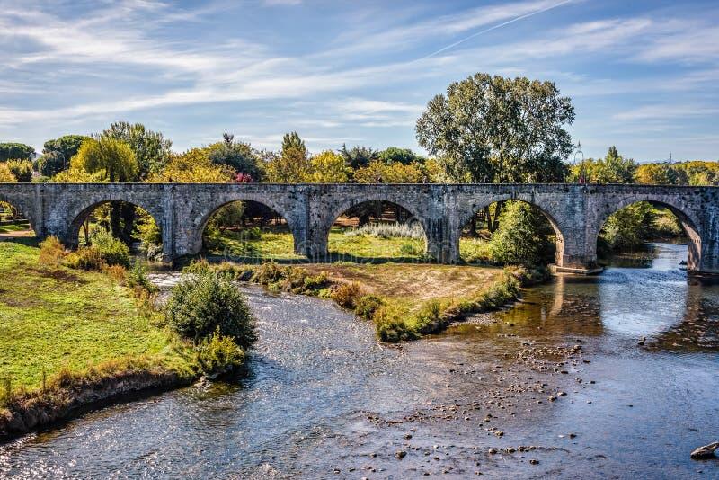 Överbrygga att leda in i en gammal medeltida stad under blåa himlar med f arkivbild