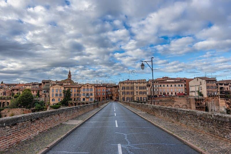 Överbrygga att leda in i en gammal stad under blåa himlar med fluffig whi royaltyfri bild