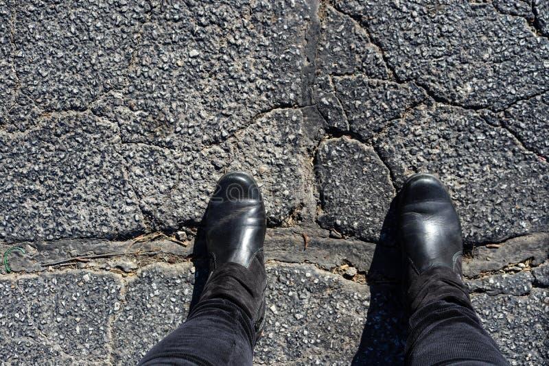 Överbrygga skiljelinjen - foten av kvinnan i svartkängor står med fot över stor reparation i sprucken asfalt arkivfoton