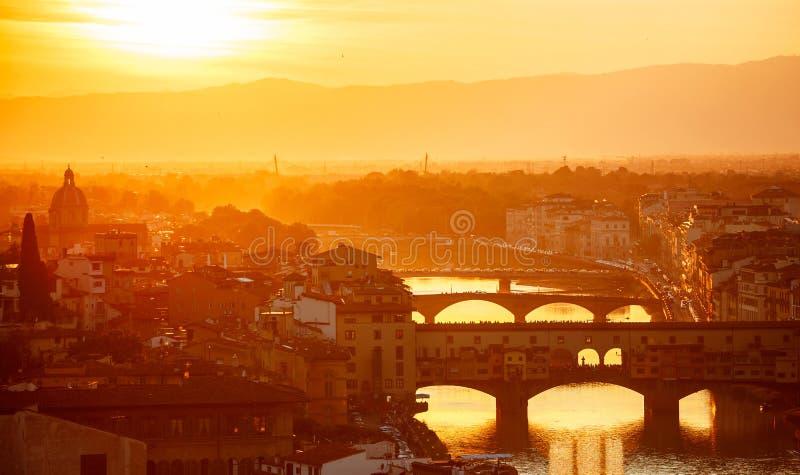 Överbryggar arno flodflorence Italien den gamla staden i aftonsolnedgång royaltyfri bild