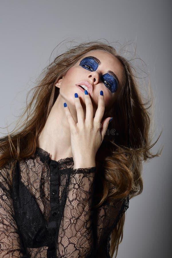 Överdrift. Älskarinna med blå dramatisk makeup och manikyr royaltyfri fotografi