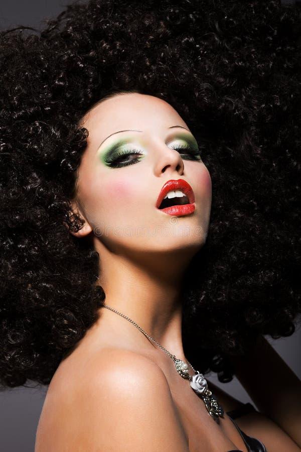 Överdrift. Kreativitet. KvinnaHipster i överdådig flätad peruk arkivfoto