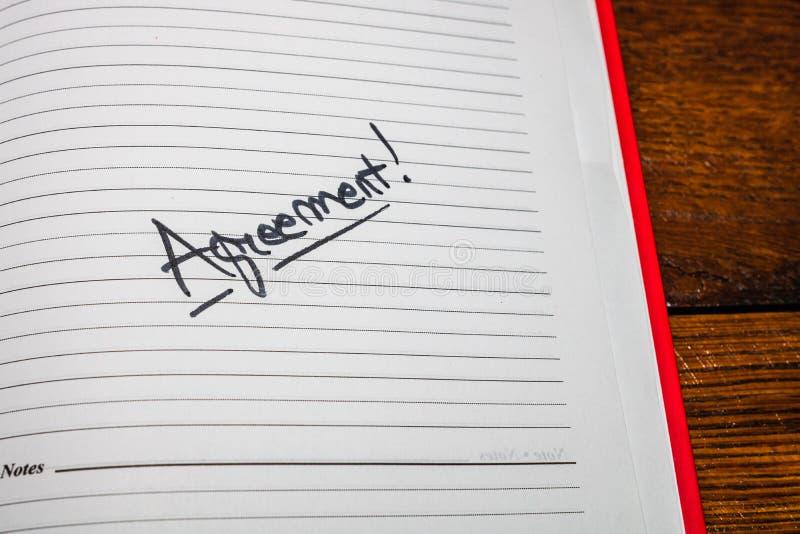Överenskommelse, handskriftstext på sidan med kontorsprogram Kopiera utrymme arkivbild