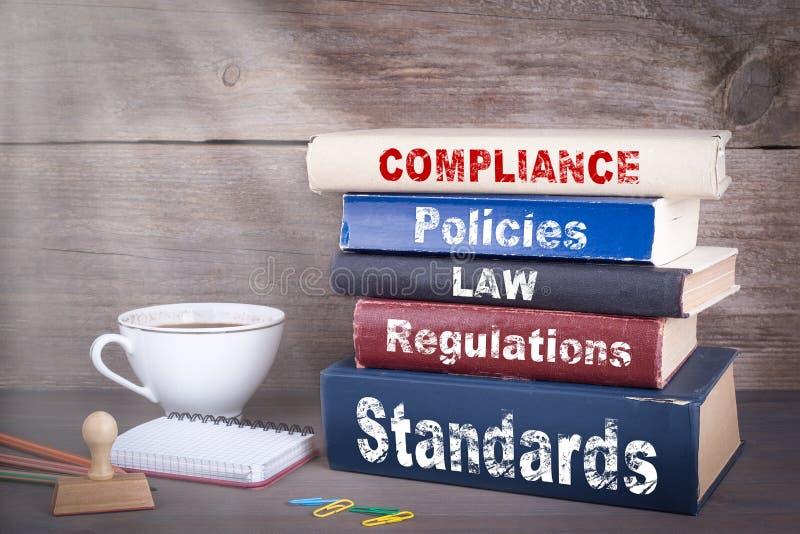 Överensstämmelsebegrepp Bunt av böcker på träskrivbordet royaltyfri fotografi