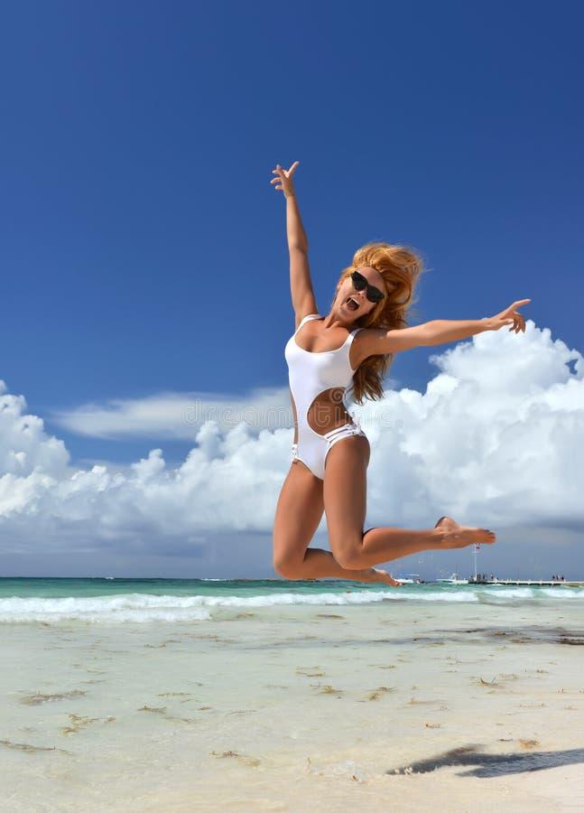 Överför den lyckliga banhoppningen för den sexiga kvinnan som kopplar av på den tropiska stranden arkivbild