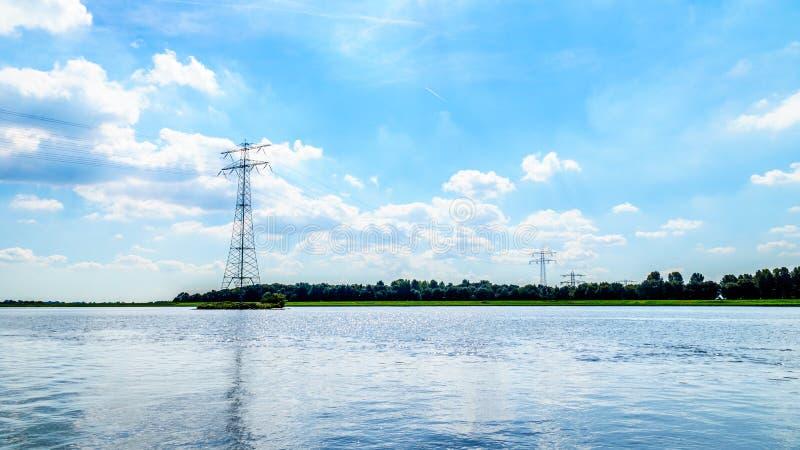Överföringslinjer som korsar Veluwemeer sjön som stöttas av den stora överföringen, står högt arkivbild