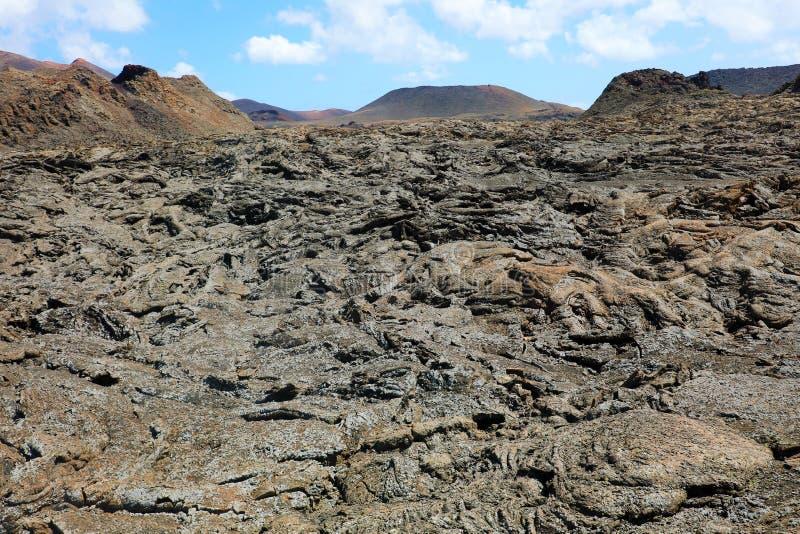 Överfört till fast form lavaflöde och skorpa med vulkaniska berg på bakgrunden i den Timanfaya nationalparken, Lanzarote, kanarie arkivbild