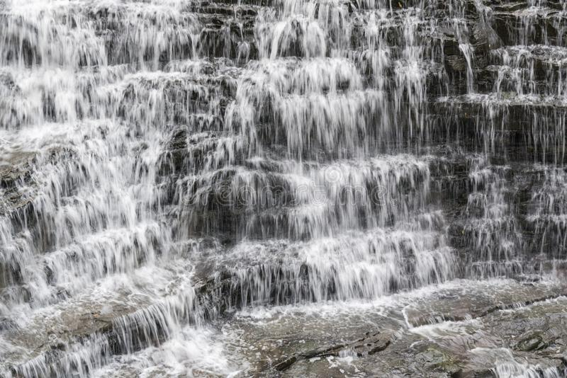 Överflödande flöda för vattenfall av att applådera vaggar i många små rader royaltyfri foto