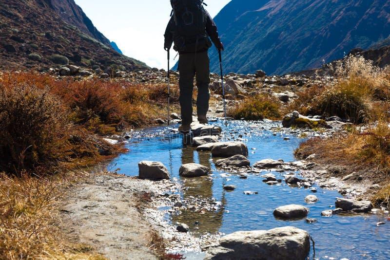 Övergående bergliten vik för fotvandrare som kliver på stenar royaltyfria foton