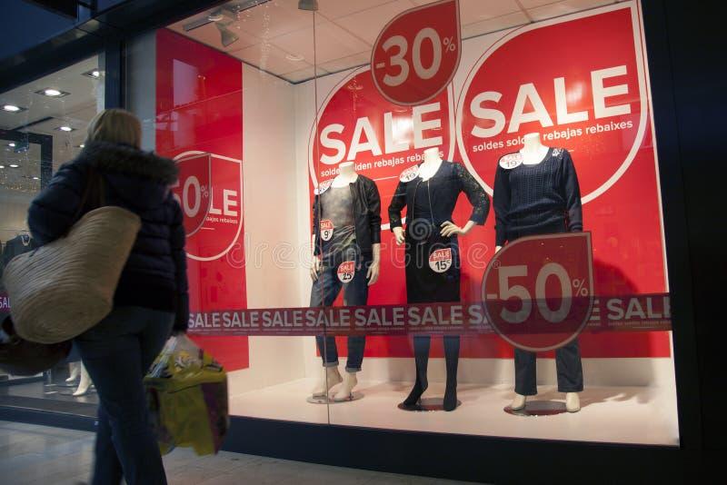 Övergående försäljning för kvinna i shoppingwndow av modelagret royaltyfri fotografi