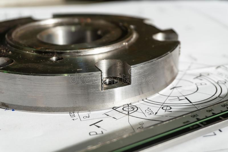 Övergångsflänsen, når den har bearbetat, ligger på den tekniska teckningen Bredvid delen är det att mäta hjälpmedlet, en klämma arkivbilder
