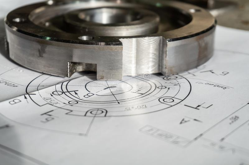 Övergångsflänsen, når den har bearbetat, ligger på den tekniska teckningen Specificera klart att arbeta med en teckning tillsamma arkivbild