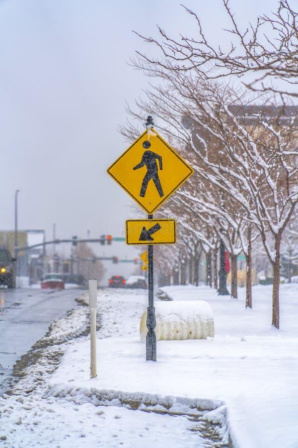 Övergångsställe tecken på en snöig trottoar arkivfoton